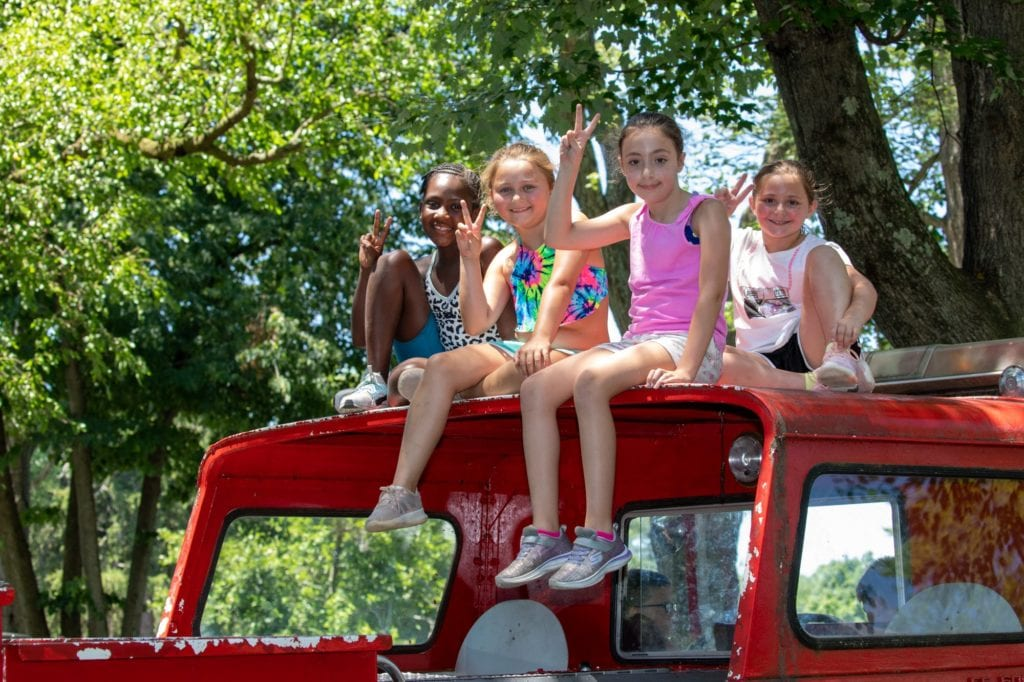 girls with peace sign on top of fire truck