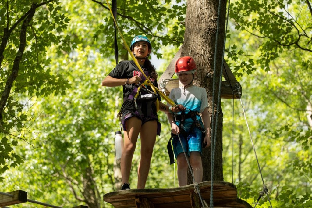 child and counselor on high ropes course